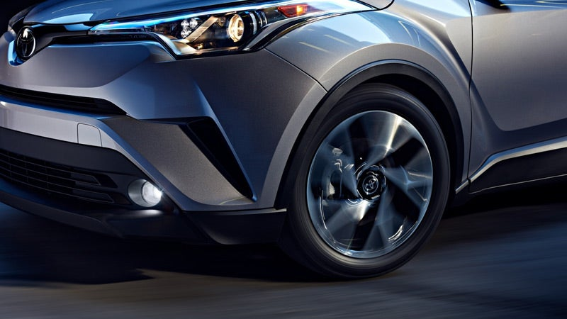 2019 Toyota CH-R Limited shown in Silver Knockout Metallic with standard projector-beam halogen headlights, unique cluster LED Daytime Running Lights (DRL) and available high-performance LED fog lights.