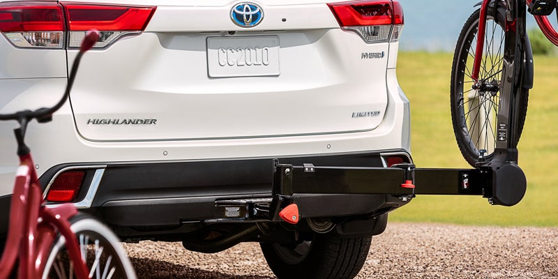 2019 Toyota Highlander Hybrid Limited shown in Blizzard Pearl with accessory tow hitch.